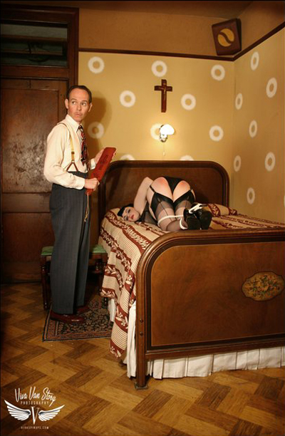 Man stands beside woman on bed with red bottom after a spanking