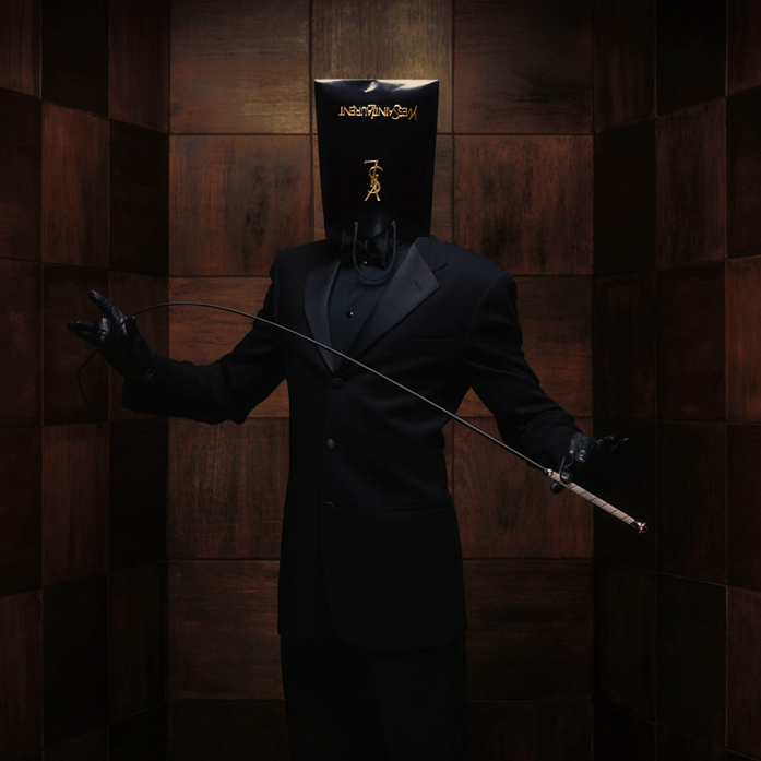 photo by Erwin Olaf of well dressed man wearing a glossy black YSL back on head